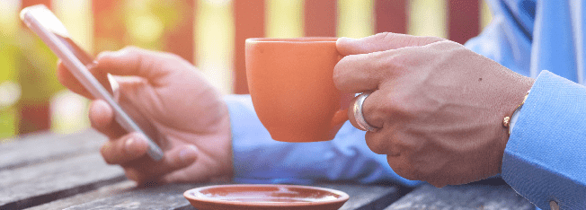 Hands resting on a table holding a mobile phone and a cup of coffee